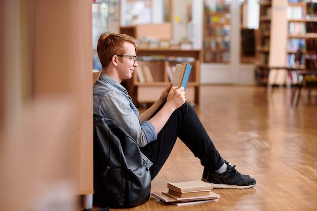 Cleverer kerl im jeanshemd und in den schwarzen jeans, die durch bücherregal in der bibliothek sitzen, während buch lesen