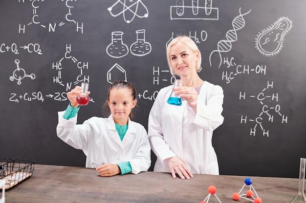 Cleveres schulmädchen und erfolgreicher chemielehrer in weißkitteln, die röhrchen mit roten und blauen flüssigkeiten auf dem tisch halten und gleichzeitig reaktion zeigen