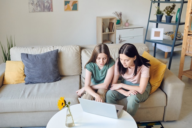 Cleveres teenager-schulmädchen, das auf das laptop-display zeigt, während sie ihrer mutter neugierige waren zeigt, die sie im online-shop bestellen wird