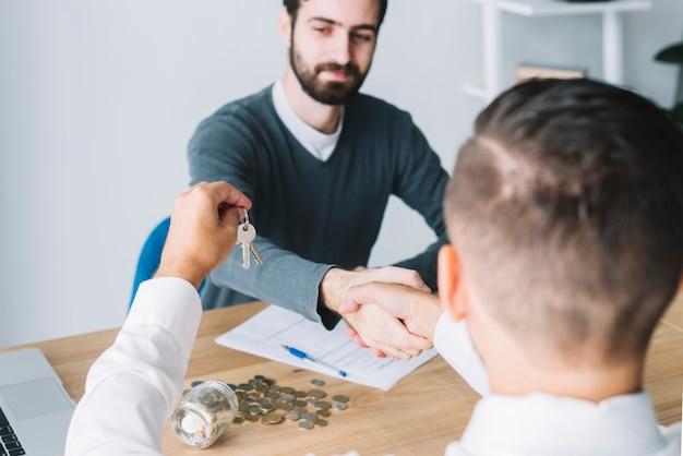 Client, der hand des agenten rüttelt und schlüssel betrachtet