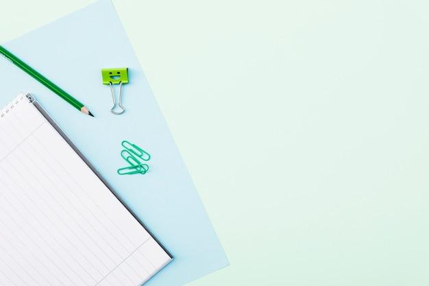 Clips und bleistift in der nähe von notebook