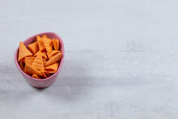 Cloe up foto von würzigen chips in lila schüssel auf weiß.