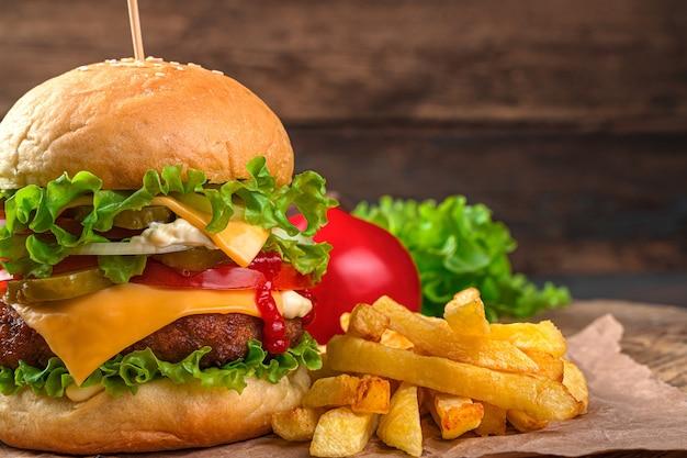 Close-up burger mit rindfleisch, käse, gemüse und sauce an der wand von pommes frites, tomate und salat. fastfood.