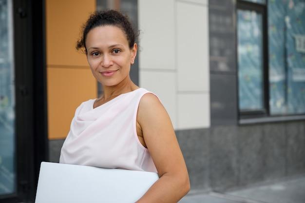 Close-up-business-porträt der attraktiven frau der gemischten rasse in freizeitkleidung mit laptop-computer, lächelnd in die kamera auf dem hintergrund der hohen gebäude. geschäfts-, freiberufler-, büroarbeitskonzept
