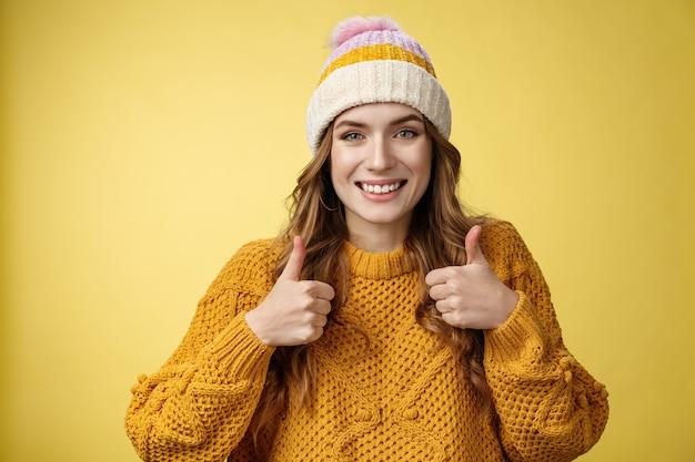 Close-up charmante unterstützende freundliche junge frau zeigt daumen hoch geste lächelnde zustimmung, die ihre idee mag, ermutigen, mitzuhalten, zufriedene gute ausgezeichnete wahl, stehend erfreut gelber hintergrund