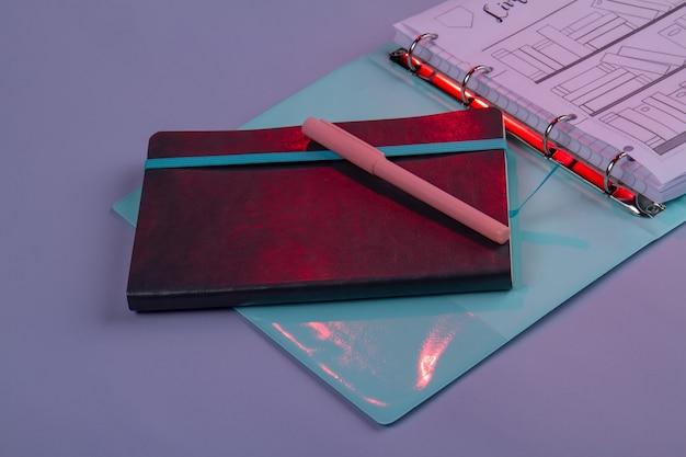 Close-up copybook mit stift und ordner mit zeichnungen. zubehör für die büroarbeit.