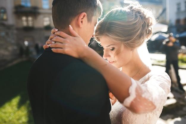Close-up der braut mit den händen um den hals des bräutigams