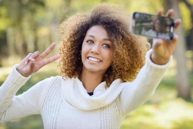 Close-up der frau mit dem lockigen haar, das ein selfie nehmen