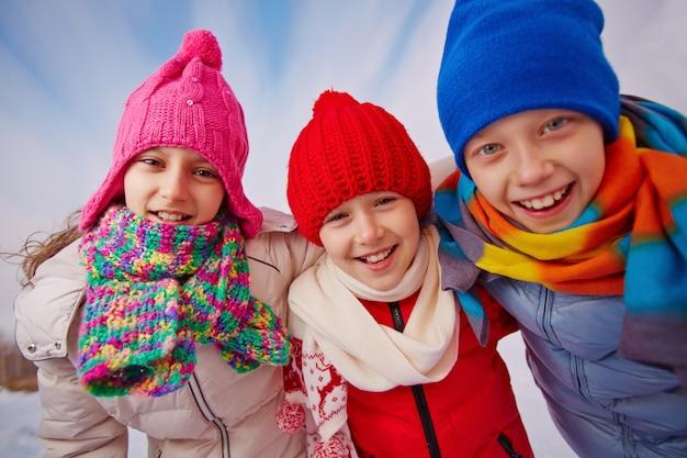 Close-up der glückliche kinder mit wollmützen und schals