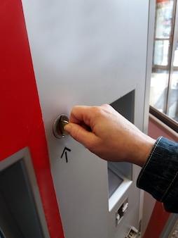 Close-up der menschlichen hand einfügen münze in automaten