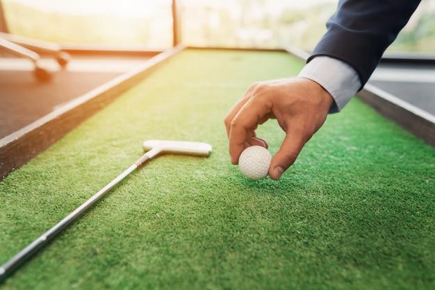 Close up ein mann in einem business-anzug spielt golf im büro