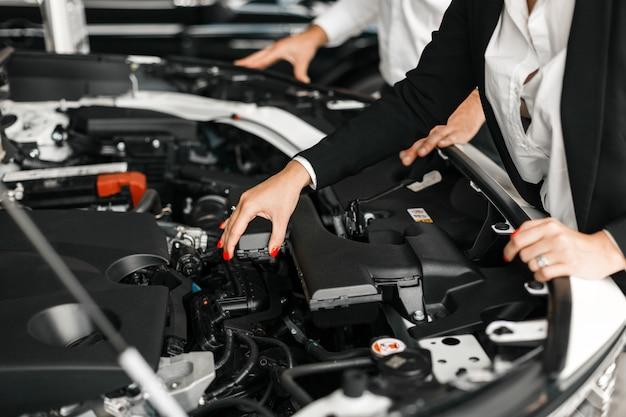 Close up eine motorhaube. weibliche hand, die einen motor berührt.
