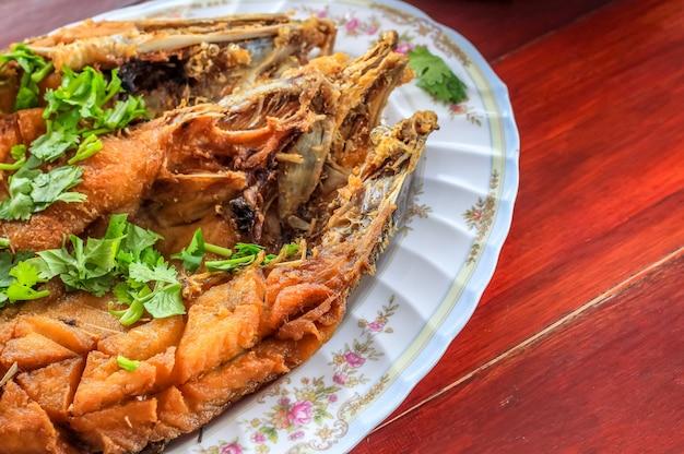Close up frittierter wolfsbarsch mit fischsauce (pla ga pong tod nam pla) in der platte mit korianderpetersilienblättern dekorieren