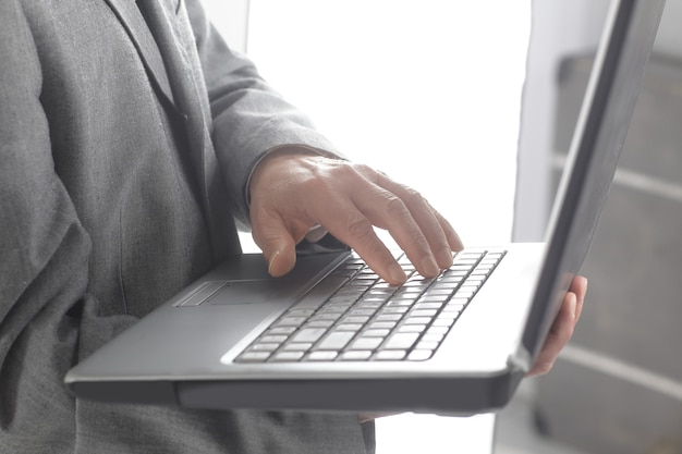 Close up.geschäftsmann, der auf einer laptop-tastatur schreibt.isoliert auf weißem hintergrund