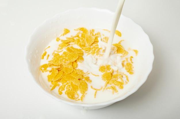 Close up gießt milch in eine schüssel mit cornflakes