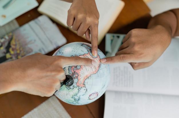 Close up gruppe von menschen zeigen einen finger auf globus