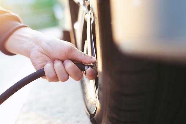 Close up hand mann auto parken einen scheck und den reifen aufpumpen die luft für sicheres fahren auf dem weg auffüllen.