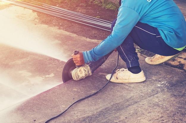 Close up hand mann schneiden betonboden mit maschine.