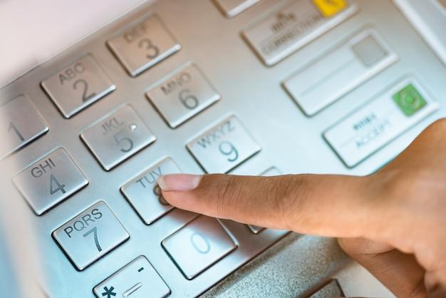 Close up hand passwort bei atm eingeben.