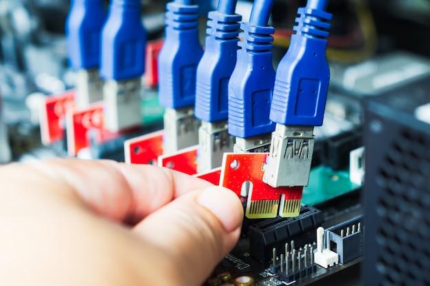 Close-up hand stecken sie ein kabel in den steckplatz, um ein gerät für den abbau von kryptowährung wie altcoins oder bitcoin zu bauen. anschlüsse auf der hauptplatine für grafikkarten.