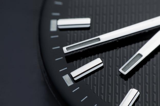 Close up im uhrzeigersinn auf schwarzem zifferblatt hintergrund. armbanduhr im retro-stil