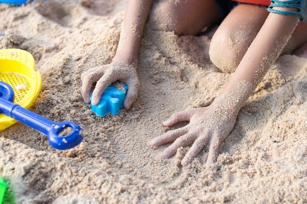 Close up kind hand spielen spielzeug am sandstrand