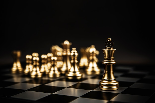 Close-up king chess steht an erster stelle im team auf dem schachbrett.