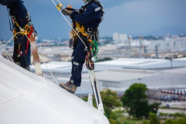 Close-up männliche zwei arbeiter kontrollausrüstung seil nach unten dachtank seilzugangsinspektion der dicke shell plate lagertank gassicherheitsarbeiten in der höhe.
