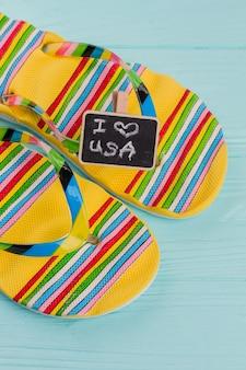 Close-up mehrfarbige sandalen mit tafel auf blauem schreibtisch. ich liebe usa auf tafel. helle sandalen aus gummi.