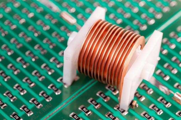 Close-up-metallkupferdraht auf einem kunststoffkorken liegt auf einem grünen mikrokreis. konzept zur herstellung leistungsstarker grafikkarten und computer sowie für das mining