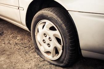 Close up Platt Reifen und altes Auto auf der Straße warten auf Reparatur