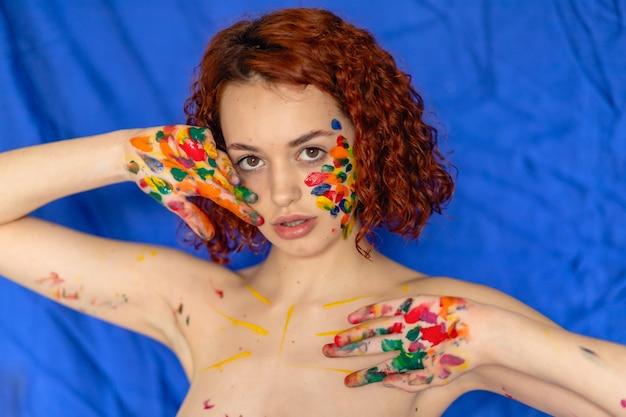 Close-up portrait von roten lockigen haaren junge fröhlich in farbe verschmutzt. porträt eines mädchens mit einem kreativen muster im gesicht. konzeptfotografie für kunst- oder frauenblog