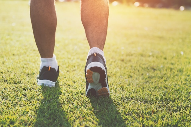 Close up runer bein läuft auf gras mit sonnenuntergang im park