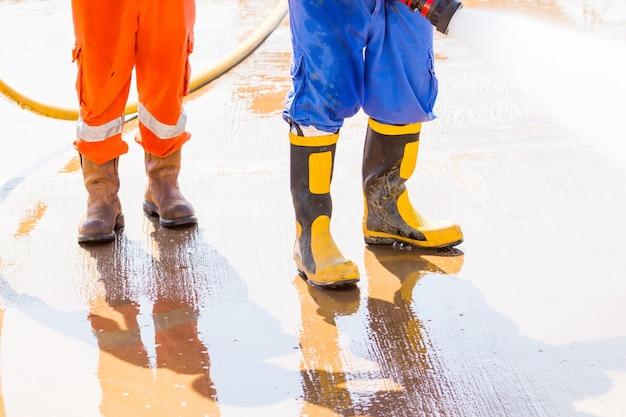 Close up safety boos.worker verwenden boot für die sicherheit der reinigung von wasser