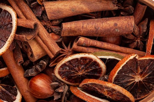 Close up schuss von gewürzen: getrocknete orangen, zimt, anis, haselnüsse. weihnachtsgewürz-konzept