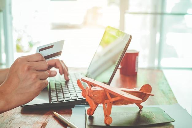 Close up seitenansicht schuss von jungen geschäftsmann arbeitet an seinem laptop und mit kreditkarte sitzen am holztisch in einem café mit vintage-filter farbton