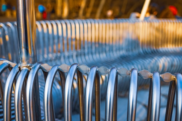 Close-up-straßenbank-metallrohre, die auf einer straßenstruktur parallel zueinander angeordnet sind. konzept für wetterbeständige materialien und modernes industriedesign. platz für werbung