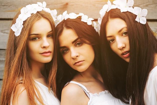 Close-up von drei jungen frauen mit blumenkränzen