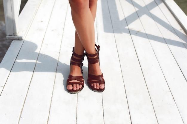 Close-up von einer frau mit braunen sandalen