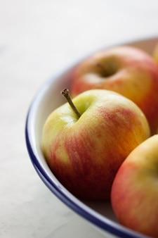 Close-up von frischen äpfeln in eine schüssel geben