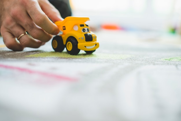 Close-up von hand mit einem gelben spielzeugauto