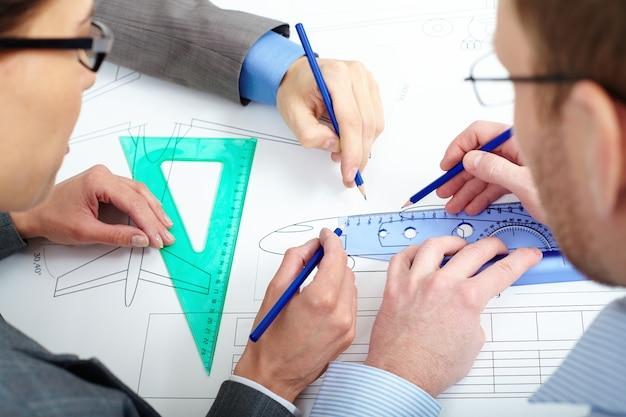 Close-up von ingenieuren die skizze zu verbessern