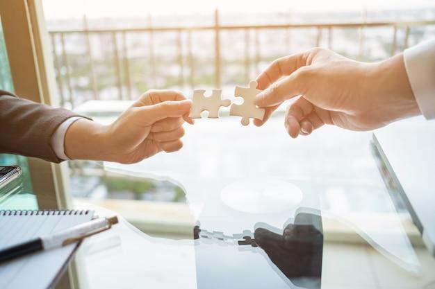 Close up zwei hände verbinden zwei puzzle. geschäfts-, erfolgs- und strategiekonzept.