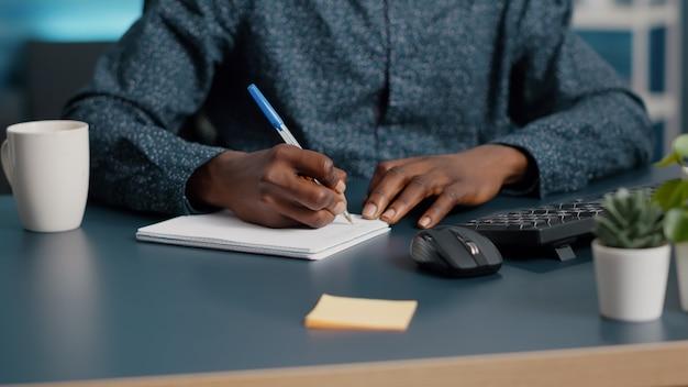 Closeup afroamerikanischer schwarzer mann hände notizen auf notizblock mit einem stift männlichen erwachsenen händen von rem...