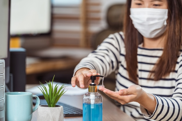 Closeup asiatische arbeiterin händedesinfektionsmittel für die reinigung ihrer hand bei der arbeit mit computer