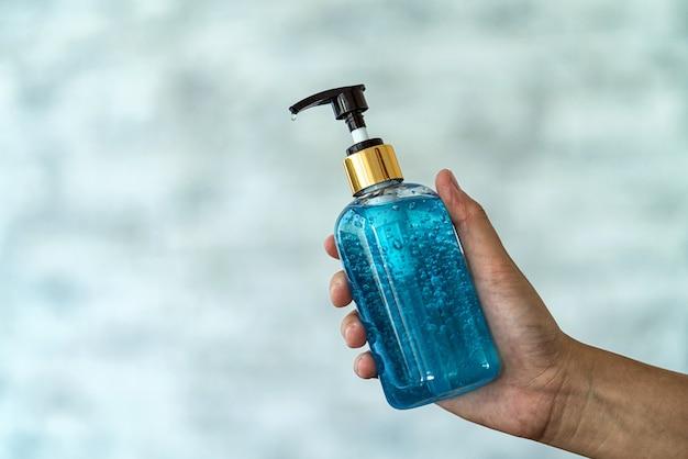 Closeup asiatische frau hand waschen händedesinfektionsgel pumpspender vor der arbeit