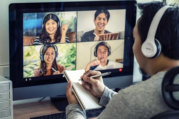 Closeup asiatischer mann hand schreiben notizbuch beim online-lernen per videokonferenz