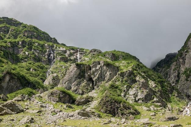 Closeup berge szenen, spaziergang zur trift bridge im nationalpark schweiz, europa. sommerlandschaft, sonnenscheinwetter, dramatischer bewölkter himmel und sonniger tag