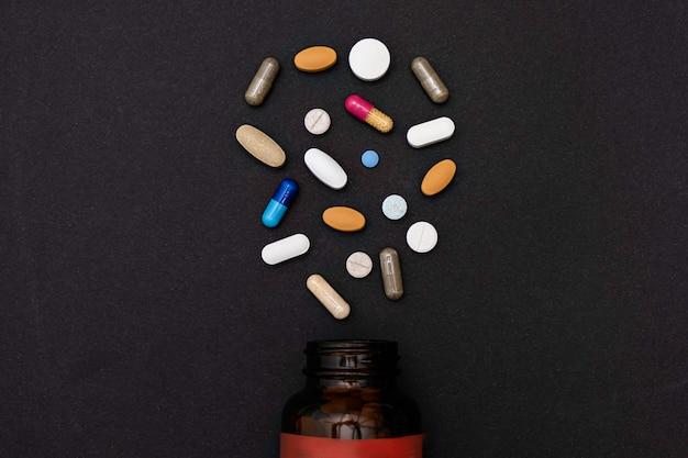 Closeup bunt sortierte pulver weichkapseln pille vitamine und glasflaschenergänzungen auf schwarz