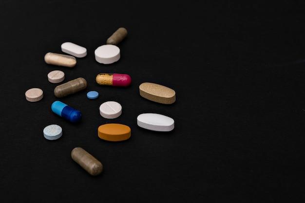 Closeup bunte pulver weichkapseln pille vitamin blau rosa gelb braun ergänzungen auf schwarz